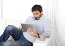Giovane uomo ispano attraente a casa sullo strato bianco facendo uso della compressa digitale o del cuscinetto Immagine Stock Libera da Diritti