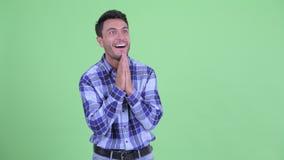 Giovane uomo ispano felice che guarda intorno e che ritiene emozionante stock footage