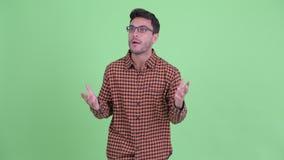 Giovane uomo ispano felice dei pantaloni a vita bassa che guarda intorno e che ritiene emozionante archivi video