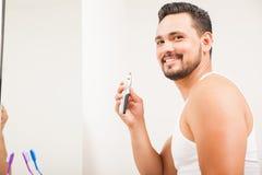 Giovane uomo latino che per mezzo di un regolatore dei capelli di naso Fotografie Stock Libere da Diritti