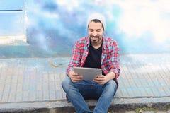 Giovane uomo latino che per mezzo di una compressa immagini stock libere da diritti