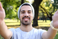 Giovane uomo latino che prende un selfie in un parco immagine stock