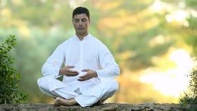 Giovane uomo latino che si siede sulla parete e sul meditare video d archivio