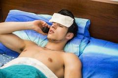 Giovane uomo malato o indisposto a letto che chiama medico Fotografia Stock