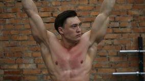 Giovane uomo muscolare che appende sulla barra stock footage