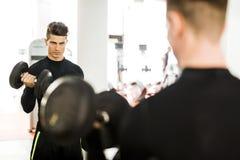 Giovane uomo muscolare che risolve in una palestra e nei pesi di sollevamento fotografie stock