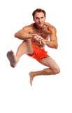 Giovane uomo muscolare che salta contro il bianco Immagini Stock Libere da Diritti