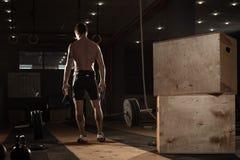 Giovane uomo muscolare che si esercita con il bilanciere Immagini Stock