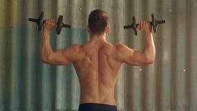 Giovane uomo muscolare che si esercita con le teste di legno video d archivio