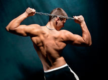 Giovane uomo muscolare con una catena isolata su oscurità Immagine Stock Libera da Diritti