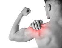 Giovane uomo muscolare di sport che tiene spalla irritata nel dolore che tocca massaggio nello sforzo di allenamento Fotografie Stock