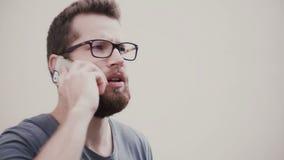 Giovane uomo nervoso di affari che parla emozionalmente sul telefono Il tipo con la barba ed i vetri hanno una rottura da lavoro  stock footage