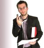 Giovane uomo occupato di affari che esamina la macchina fotografica che tiene un pho delle cellule Fotografie Stock Libere da Diritti
