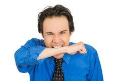 Giovane uomo pazzo sembrante pazzo che rincoglionisce il braccio mordace del polso Fotografia Stock Libera da Diritti
