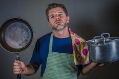 Giovane uomo pigro sollecitato ed enorme attraente con la pentola della cucina della tenuta del grembiule ed il vaso del cuoco ne immagine stock libera da diritti