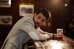 Giovane uomo potabile che si siede al contatore in un pub fotografie stock libere da diritti