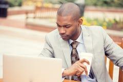 Giovane uomo premuroso bello di affari che lavora al computer portatile all'aperto Immagini Stock