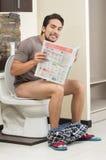 Giovane uomo rilassato che si siede sulla lettura della toilette Fotografia Stock