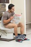 Giovane uomo rilassato che si siede sulla lettura della toilette Fotografie Stock Libere da Diritti