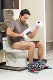 Giovane uomo rilassato che si siede sulla lettura della toilette Immagine Stock Libera da Diritti