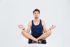 Giovane uomo rilassato di forma fisica che si siede nella posa e nel meditare del loto Immagine Stock Libera da Diritti