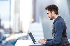 Giovane uomo romantico che lavora al suo computer portatile nella città Immagine Stock Libera da Diritti