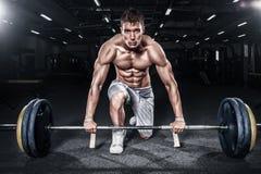 Giovane uomo senza camicia atletico di sport - il modello di forma fisica tiene il bilanciere in palestra Copi la parte anteriore fotografia stock