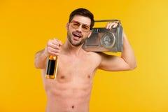 giovane uomo senza camicia in occhiali da sole che tengono bottiglia della bevanda e del registratore di estate e che sorridono a fotografie stock