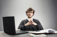 Giovane uomo serio che si siede nel suo posto di lavoro fotografia stock libera da diritti