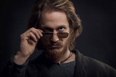 Giovane uomo serio con la barba e baffi che esaminano i suoi occhiali da sole Fotografia Stock