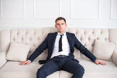 Giovane uomo serio e sicuro in un vestito che si siede sullo strato Fotografia Stock Libera da Diritti