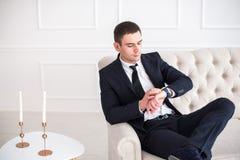 Giovane uomo serio e sicuro in vestito che si siede sul sofà e che esamina orologio Immagini Stock