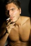 Giovane uomo sexy che fuma una sigaretta Immagine Stock