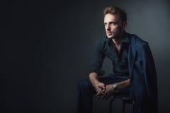 Giovane uomo sexy in un vestito classico che si siede su una sedia Fotografia Stock