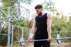 Giovane uomo sicuro di forma fisica che fa gli esercizi con il bilanciere Immagine Stock