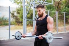 Giovane uomo sicuro di forma fisica che fa gli esercizi con il bilanciere Fotografie Stock