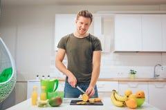 Giovane uomo sorridente che cucina frutta fresca nella cucina Alimento sano Pasto vegetariano Disintossicazione di dieta immagine stock