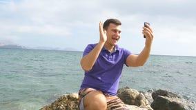 Giovane uomo sorridente che ha una video chiamata sullo Smart Phone alla spiaggia del mare Tipo felice che fa le video chiacchier Immagine Stock