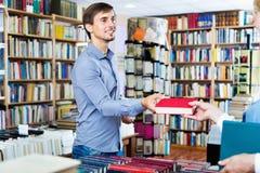 Giovane uomo sorridente che prende libro scelto dal venditore Fotografia Stock Libera da Diritti