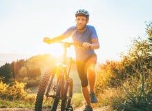 Giovane uomo sorridente che spinge un mountain bike sulla collina Viaggio attivo di avventura sulla bicicletta fotografia stock libera da diritti