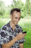 Giovane uomo sorridente con il telefono mobile Immagini Stock Libere da Diritti