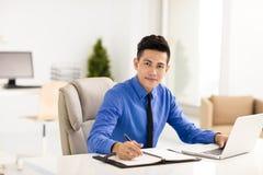 Giovane uomo sorridente di affari che lavora nell'ufficio Immagine Stock