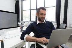 Giovane uomo sorridente di affari che per mezzo del computer portatile Immagini Stock