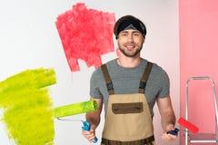 giovane uomo sorridente nel lavoro complessivo con i rulli di pittura davanti al dipinto a fotografia stock