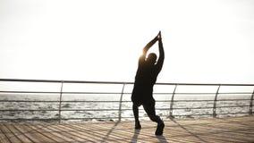 Giovane uomo sportivo che allunga fuori sul bacino vicino alla spiaggia Bella mattina soleggiata del litorale sul metraggio all'a archivi video