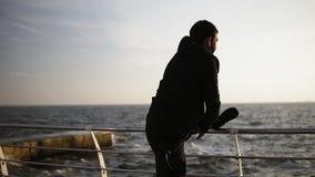 Giovane uomo sportivo che allunga fuori sul bacino vicino alla spiaggia Bella mattina soleggiata del litorale sul metraggio all'a stock footage