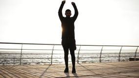 Giovane uomo sportivo che si esercita sul bacino vicino alla spiaggia Bella mattina soleggiata del litorale sul metraggio all'ape video d archivio