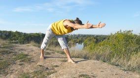 Giovane uomo sportivo che sta alla posa di yoga all'aperto L'yoga di pratica del tipo caucasico si muove e posiziona in natura Be Fotografia Stock Libera da Diritti