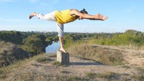 Giovane uomo sportivo che sta alla posa di yoga all'aperto L'yoga di pratica del tipo caucasico si muove e posiziona in natura at Fotografia Stock
