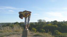 Giovane uomo sportivo che sta alla posa di yoga all'aperto L'yoga di pratica del tipo caucasico si muove e posiziona in natura at Immagini Stock